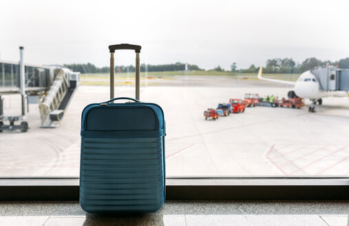Suitcase at the airport, passenger airplane and luggage vehicle in the background - MGOF001951