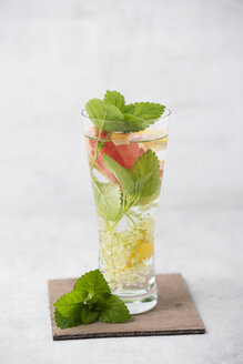 Glass of water flavoured with elderflowers, lemon, grapefruit and lemon balm - MYF001507