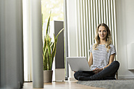 Woman at home sitting on floor with laptop - SBOF000088