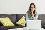 Woman at home sitting on couch with laptop - SBOF000094