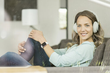 Smiling woman at home on couch wearing headphones - SBOF000100