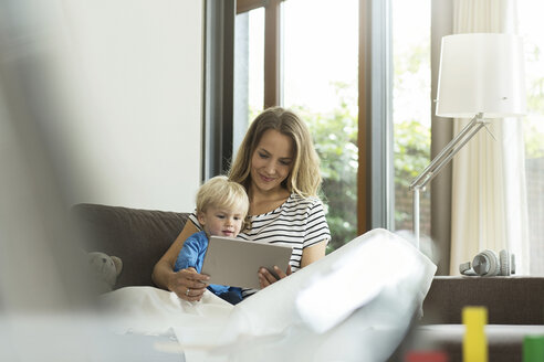 Mother and son on couch with digital tablet - SBOF000103