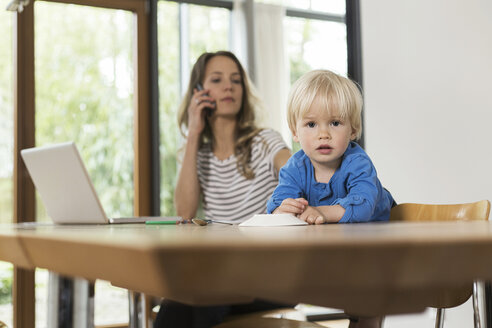 Mother with laptop on cell phone and son in foreground - SBOF000106