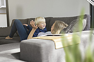 Mother and son at home playing on couch - SBOF000112