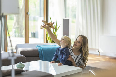 Mother and son playing with toy plane in living room - SBOF000118