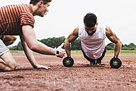 Athlete doing pushups with dumbbells on sports field supported by his training partner - UUF007714