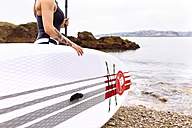 Woman with stand up paddle board at the coast - MGOF001952