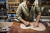 Luthier manufacturing a guitar in his workshop - ABZF000699