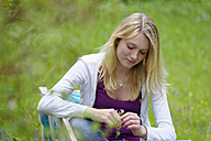 Portrait of daydreaming blond woman sitting on a bench in nature - LBF001433