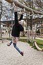 Girl using equipment on playground - TCF004981