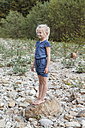 Smiling little girl standing on a rock in nature - TCF004996