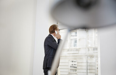 Businessman in his office telephoning with smartphone while looking through window - RHF001609