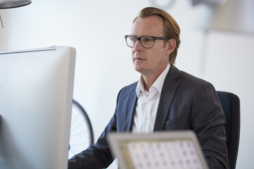 Portrait of businessman with glasses working at computer - RHF001618