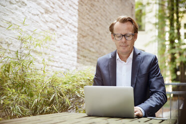 Businessman sitting at table in a backyard working with laptop - RHF001627