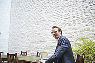 Businessman sitting with laptop at table in a backyard - RHF001630