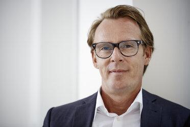 Portrait of smiling businessman wearing glasses - RHF001633
