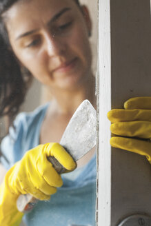 Young woman renovating old window - BZF000302