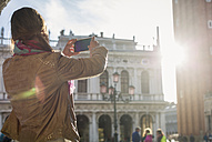 Italy, Venice, Tourist taking pictures with smart phone against the sun - MAUF000658