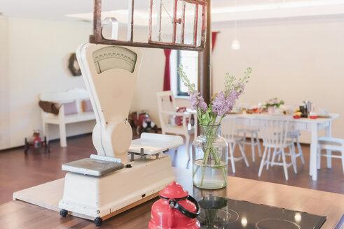 Flowers and vintage kitchen scales on kitchen island - MJF001829