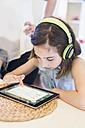 Girl wearing headphones using digital tablet - MJF001889