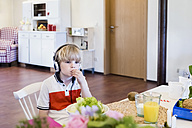 Boy wearing headphones sitting at table - MJF001895