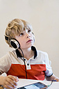 Boy wearing headphones looking up - MJF001898
