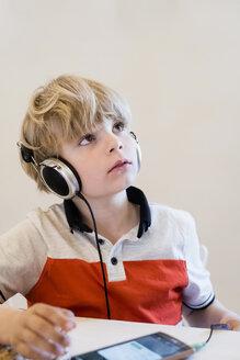 Boy wearing headphones looking up - MJF001898