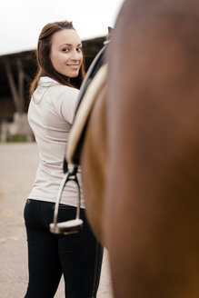 Portrait of smiling young woman with brown horse - MIDF000738