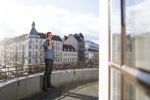Young man on cell phone on roof terrace - FKF001886