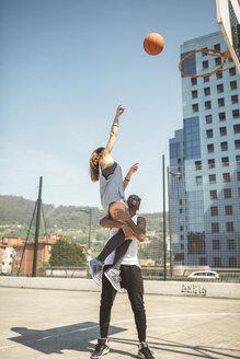 Young couple playing basketball on court - DAPF000160