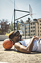 Young couple using virtual reality glasses, resting heads on basketball - DAPF000172