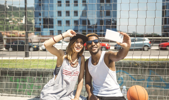 Young couple taking selfie at basketball court - DAPF000175