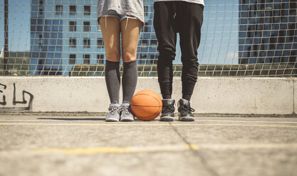 Young man and woman standing on basketball field with between their feet - DAPF000184