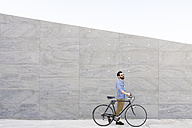 Young man with bicycle in front of grey wall - FMOF000007