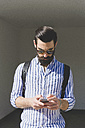 Bearded young man looking at his smartphone - FMOF000010
