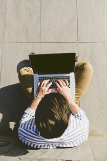 Young man sitting on the ground using laptop - FMOF000016