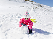 Girl building a snowman - MGOF001963