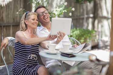 Couple sitting together at outdoor cafe looking at tablet - ZEF008782