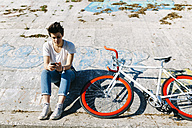 Young woman with bicycle and cell phone - GIOF001218