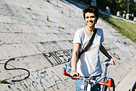 Smiling young woman with bicycle - GIOF001221