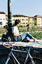 Young woman with bicycle sitting on bridge listening to music - GIOF001233