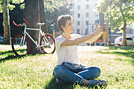 Smiling young woman sitting on meadow taking a selfie with digital tablet - GIOF001239