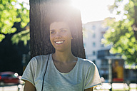 Smiling young woman at tree trunk wearing headphones - GIOF001242