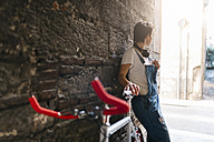 Young woman with bicycle leaning against stone wall - GIOF001248
