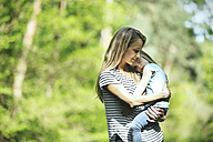 Mother carrying daughter in forest - SBOF000127