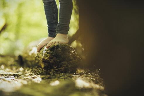 Girl in forest standing on log - SBOF000142