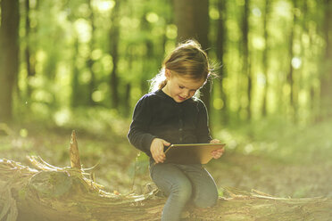 Girl in forest using digital tablet - SBOF000160