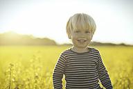 Portrait of smiling boy in canola field - SBOF000169