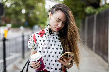Portrait of young woman with coffee to go looking at her smartphone - MAUF000663