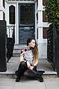 UK, London, young woman sitting on step of pavement - MAUF000669